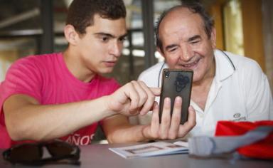 joven y anciano mirando un móvil